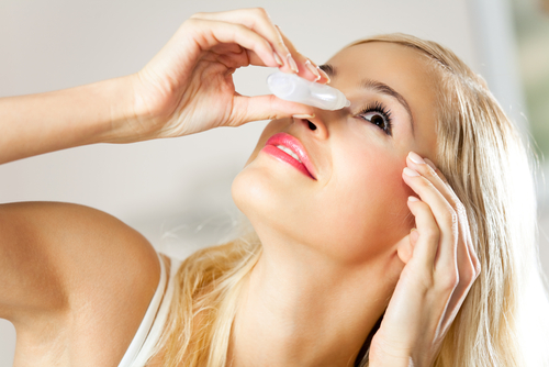 Women treating dry eye with eye drops