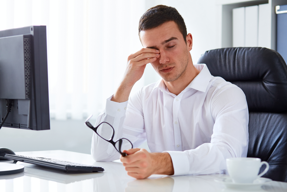 Guy sitting at desk wiping eyes with hand.