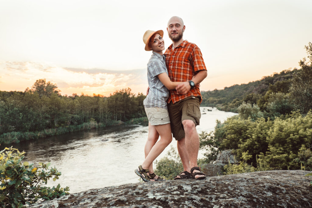 Couple looking at camera standing on top of rock.