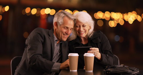 Older couple smiling while looking at cell phones.