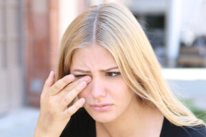 girl itching eye from dry eye