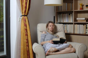 Girl reading book in chair