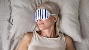 woman in bed with sleep mask on