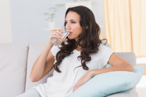 woman sitting on the couch while drinking a glass of water