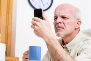 man sitting at table holding cup of coffee in one hand while holding cell phone close to his face