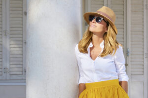 smiling woman wearing tan round hat and sunglasses along with white shirt and yellow skirt while leaning up against a pillar