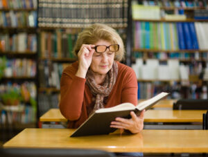 Woman looking under her glasses at book