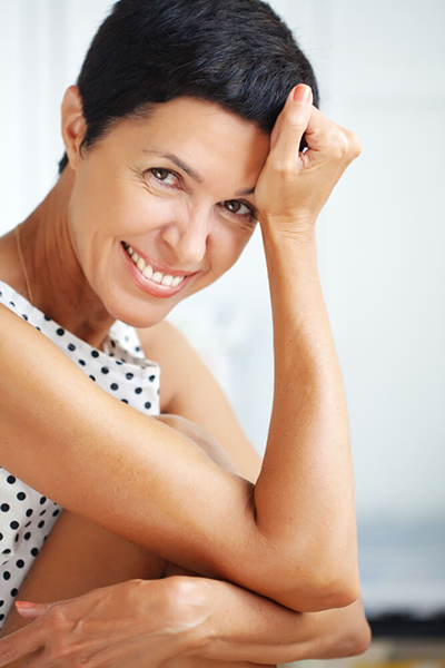 Woman With Hand on Head Smiling